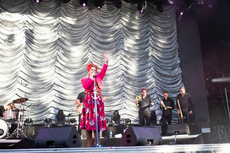 Silya på scenen i knalle farger og med fullt band.