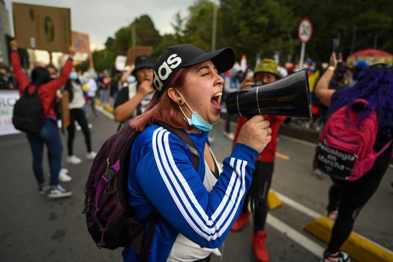 Folk protesterer mot myndighetene i Bogota i Colombia 8. mai. En kvinne roper i en megafon.