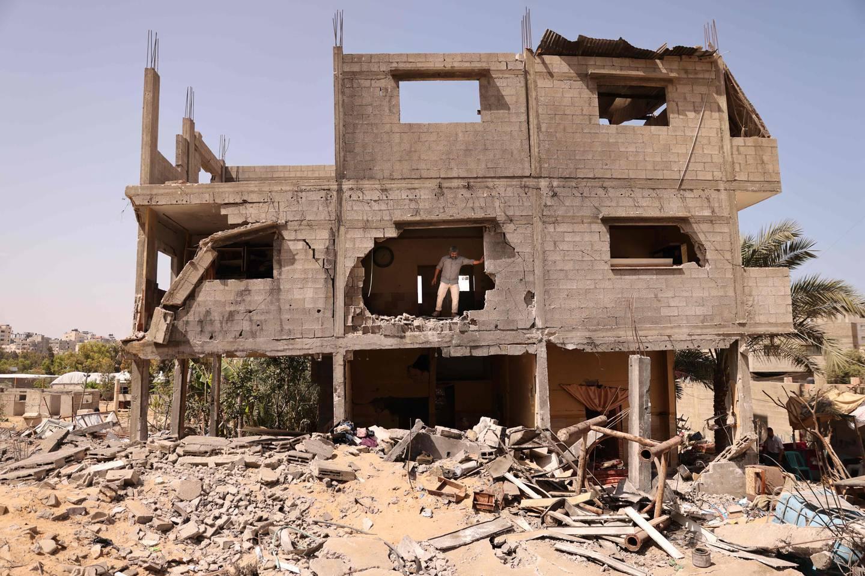 Palestinske Mansour Abu Ghadyan står i hjemmet sitt som ble ødelagt i israelske bombeangrep i Gaza by.