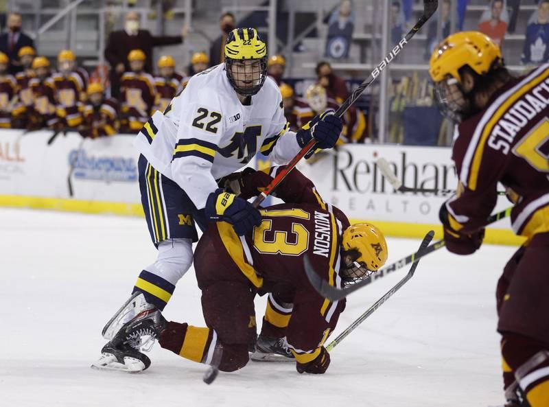 Owen Power (i hvitt) i aksjon for Michigan i NCAA. Han ble førstevalget i NHL-draften natt til lørdag. Foto: Al Goldis / AP / NTB.