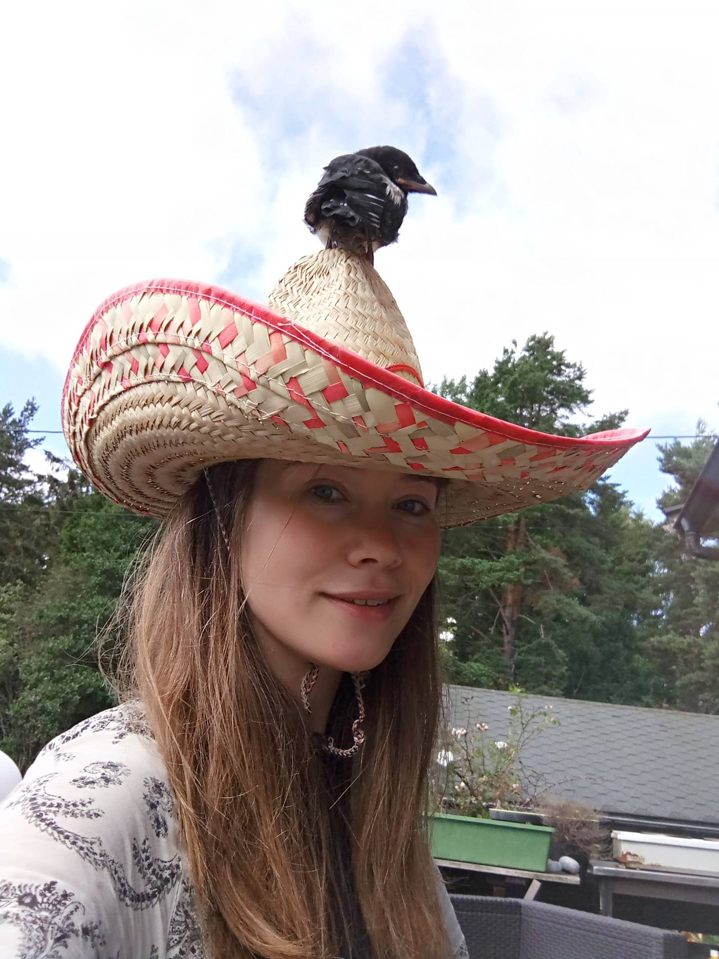 Skjæreunge sitter på toppen av en sombrerohatt, som Eli Anne har på hodet.