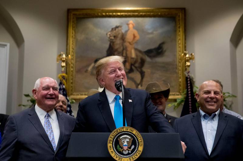 President Donald Trump, accompanied by Agriculture Secretary Sonny Perdue, left, smiles during a meeting to support America's farmers and ranchers in the Roosevelt Room of the White House, Thursday, May 23, 2019, in Washington. (AP Photo/Andrew Harnik)