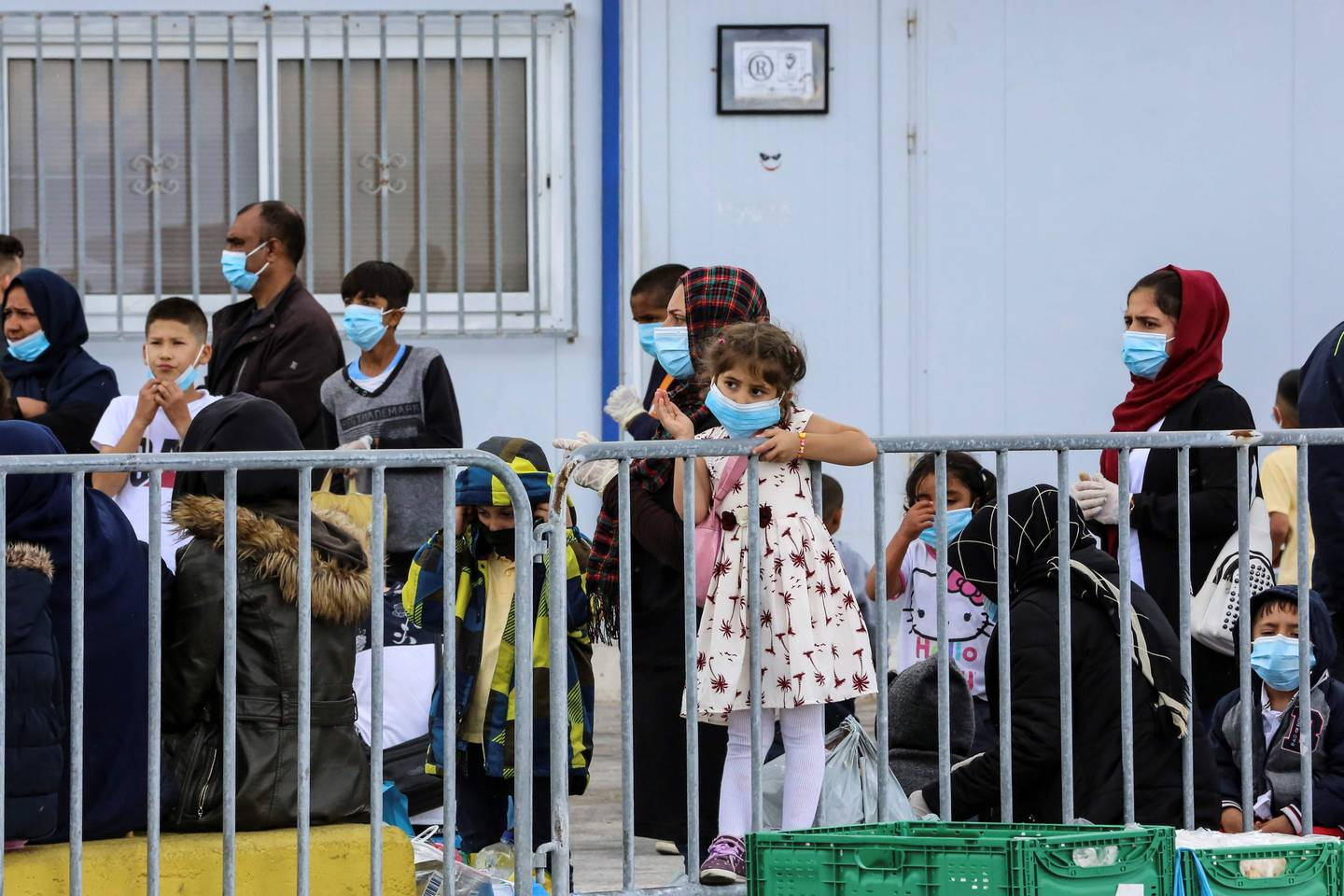 """(FILES) In this file photo taken on May 3, 2020 migrants wait at the port of Mytilene to be transferred from the island of Lesbos to the Greek main land in Moria. - Greece will extend to May 21 a coronavirus lockdown imposed since March on migrant camps and which had been expected to be lifted from May 11, 2020, the authorities said. """"The coronavirus measures of confinement for those living in migrant camps and in reception centres in Greece are prolonged until May 21,"""" the migration and asylum ministry said in a statement on Sunday, six days after the first easing of the general lockdown in the country. The ministry did not say why the camp lockdown was being extended. (Photo by Manolis Lagoutaris / AFP)"""