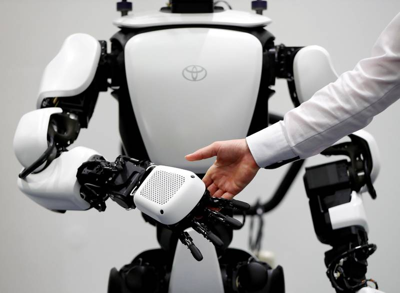 An employee of Toyota Motor Corp. demonstrates T-HR3 humanoid robot which will be used to support the Tokyo 2020 Olympic and Paralympic Games, during a press preview in Tokyo, Japan July 18, 2019. Picture taken July 18, 2019.  REUTERS/Issei Kato