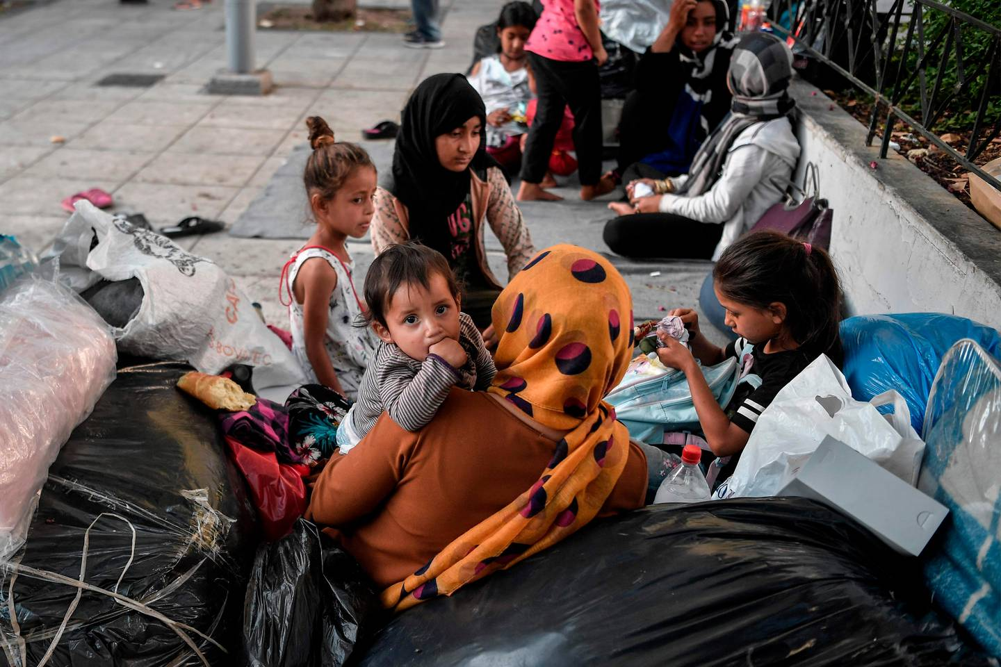 A child looks on as Afghan families who arrived, from Moria camp on the island of Lesbos camp, at an central Athens square on June 14, 2020 after receiving a blue stamp which allowed them to travel to the mainland. - At least 66 refugees, who arrived from the island after their asylum applications where approved, camp on the square as they have no place to stay in Athens. (Photo by Louisa GOULIAMAKI / AFP)