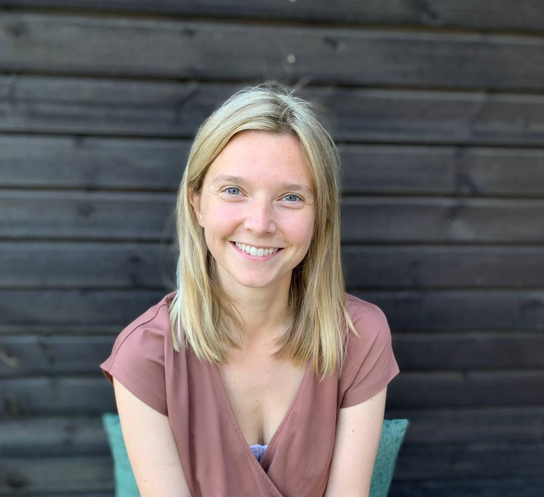 En smilende Emilie Berg Slangsvold, foran mørk vegg