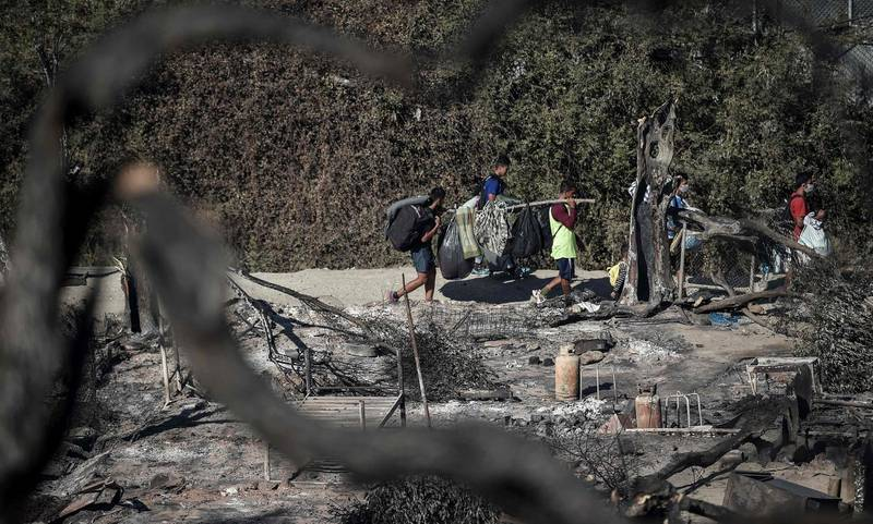 A picture taken on September 10, 2020 in Moria shows migrants carrying their belongings through the Moria refugee camp, two days after Greece's biggest and most notorious migrant camp, was destroyed by fire. - Thousands of asylum seekers on the Greek island of Lesbos languished on roadsides on Thursday, homeless and hungry after the country's largest camp burned down, with local officials stonewalling government efforts to create new temporary shelters. (Photo by LOUISA GOULIAMAKI / AFP)