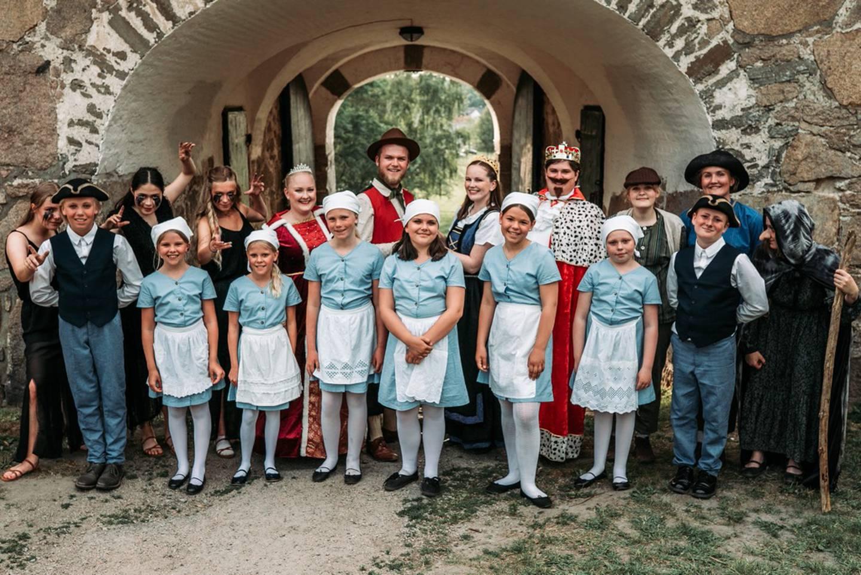 Barn og unge utkledd som forskjellige eventyrroller står foran en vollport i Gamlebyen Fredrikstad