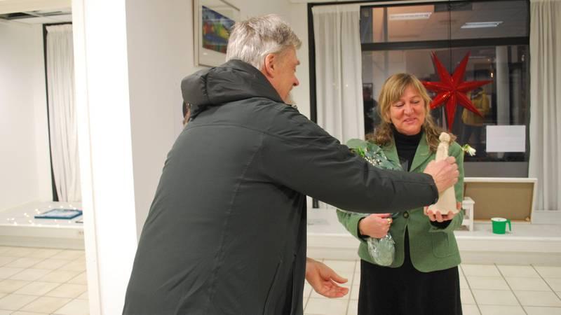 Einar Hjørleifsson overrekker det synlige beviset på at Sandberg er tildelt årets lokale fredspris, som besto av blomster og en keramikkskulptur laget av den lokale kunstneren Vibeke Åmli.