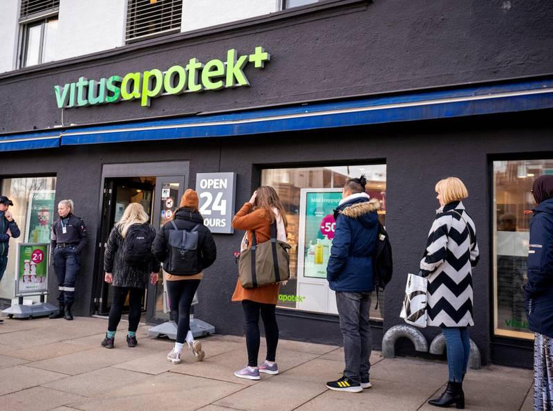 Folk står i kø utenfor Vitus Apotek på Jernbanetorget for å kjøpe medisiner på grunn av koronavirusutbruddet i Oslo. Foto: Heiko Junge/NTB scanpix