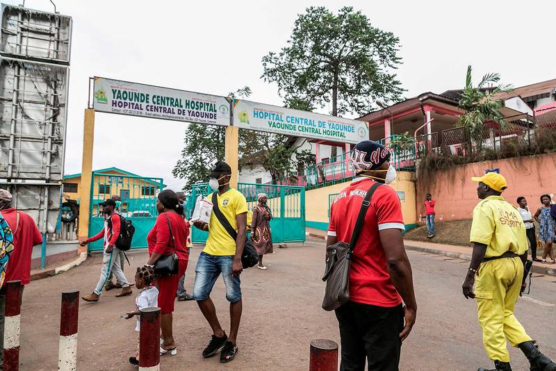 Some people wear masks as they walk by the entrance to the Yaounde General Hospital in Yaounde on March 6, 2020 as Cameroon has confirmed its first case of the COVID-19 coronavirus, a French national who arrived in the capital Yaounde in February, the government said on today. - The man, 58, has been placed in isolation in a hospital, the health ministry said in a statement. In sub-Saharan Africa, Senegal has registered four cases, all foreign nationals, and South Africa and Nigeria have one case each since the outbreak emerged in December in China. (Photo by STRINGER / AFP)