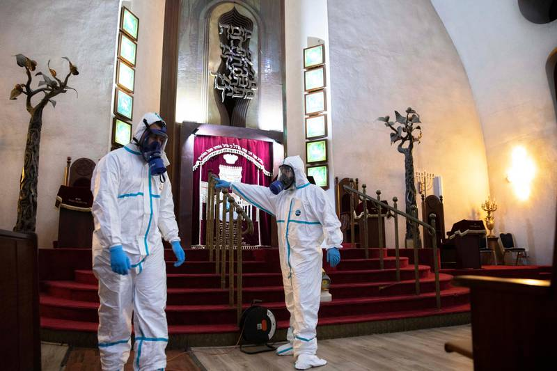 Workers sprays disinfectant as a precaution against the coronavirus at the Great Synagogue in Tel Aviv, Israel, Tuesday, March 17, 2020. The head of Israel's shadowy Shin Bet internal security service said Tuesday that his agency received Cabinet approval overnight to start deploying its counter-terrorism tech measures to help curb the spread of the new coronavirus in Israel. For most people, the virus causes only mild or moderate symptoms. For some it can cause more severe illness. (AP Photo/Sebastian Scheiner)