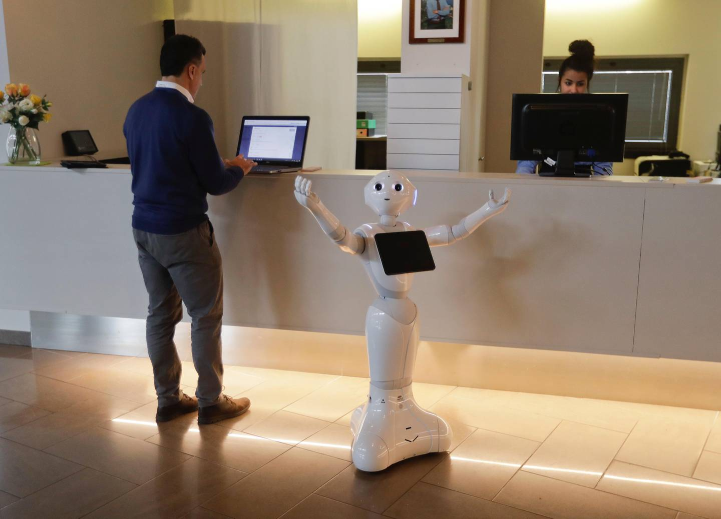 Robot Robby Pepper stands at the front desk of hotel in Peschiera del Garda, northern Italy, Monday, March 12, 2018. Robby Pepper, billed as Italy?Äôs first robot concierge, has been programed to answer simple guest questions in Italian, English and German, the humanoid, speaking robot will be deployed all season at a hotel on the popular Garda Lake to help relieve the desk staff of simple, repetitive questions. Standing at left is Jampaa Innovative digital services product manager Marco Vescovi. (AP Photo/Luca Bruno)