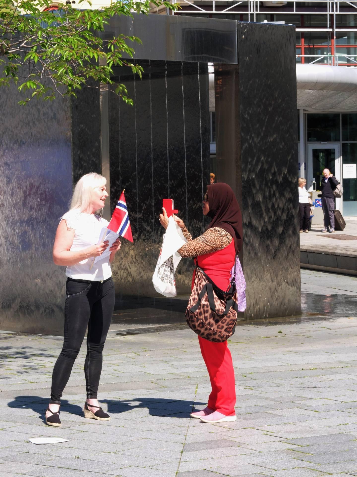 Anna Bråten deler ut flyere med SIANS budskap. Det settes ikke særlig pris på av forbipasserende som denne kvinnen i hijab, og diskusjonen blir raskt opphetet. FOTO: KATRINE STRØM