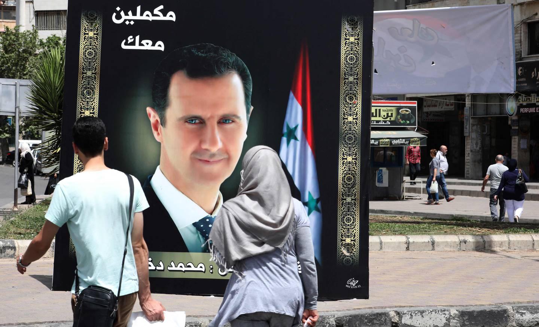Syrias president Bashar al-Assad på en valgplakat med teksten «Vi fortsetter med dere» nær Arnous-torget i Damascus den 10 mai 2021, i forkant av presidentvalget i landet.