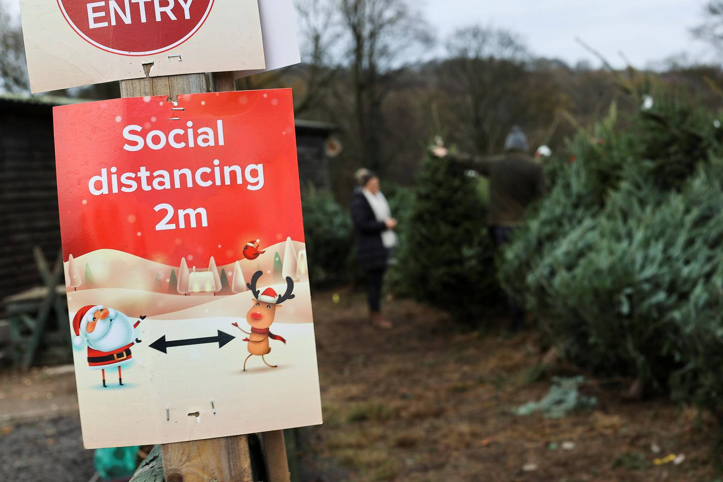 A social distancing sign is pictured as people visit a Christmas Tree Farm, amidst the outbreak of the coronavirus disease (COVID-19), in Keele, Staffordshire, Britain November 24, 2020. REUTERS/Carl Recine