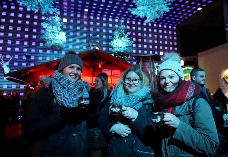 Studentene Laura, Leonie og Isabella nyter en varm eplepunsj på utendørsklubben Winterdeck på Santa Pauli-markedet.