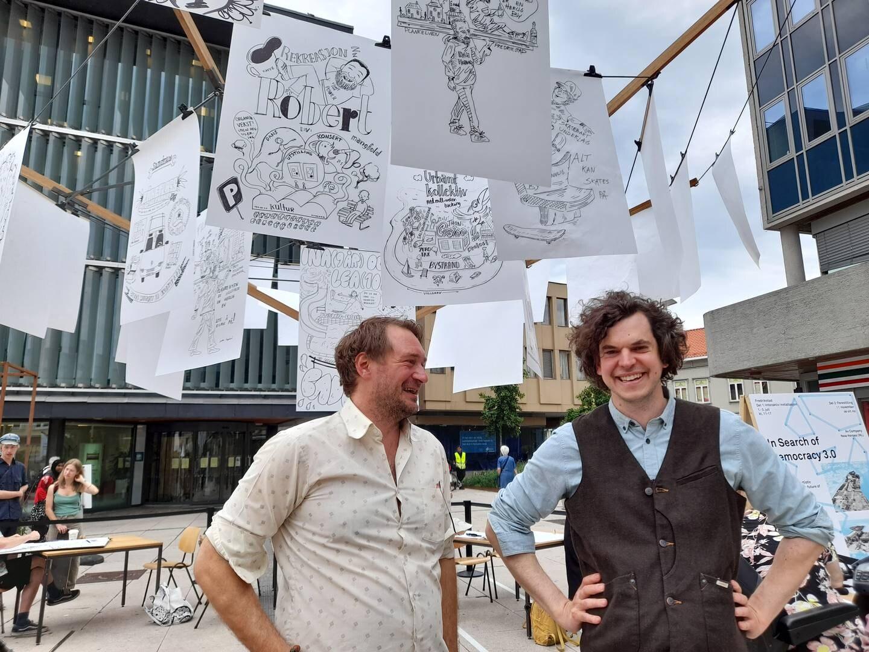 Produksjonkoordinator Fredrik Borgund og sjef for Østfold Internasjonale Teater Thomas Østgaard foran utstillingen.