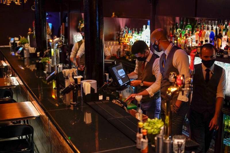 Ansatte på baren The Piano Works i London forbereder seg på gjenåpning. Foto: Alberto Pezzali / AP / NTB