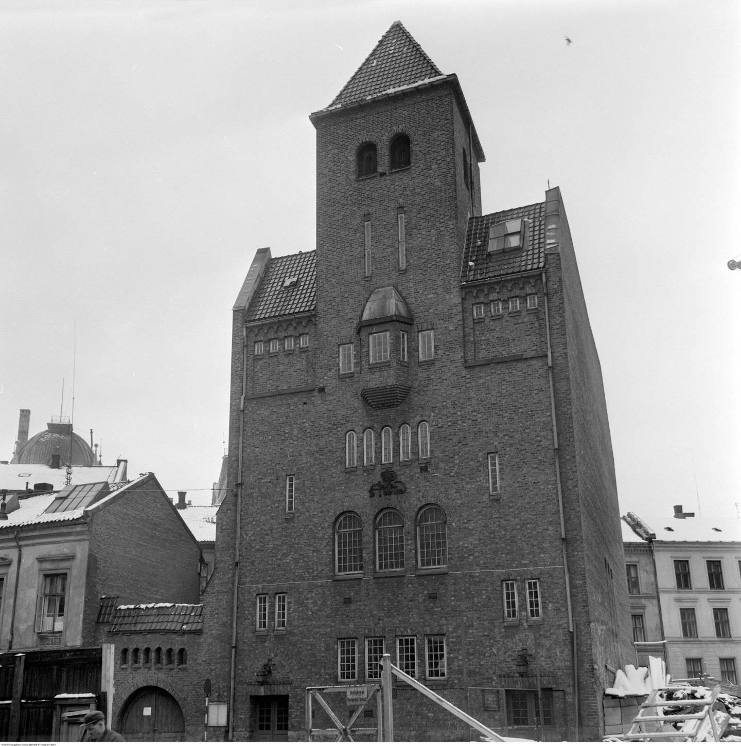 Pipervikens Småkirke i Munkedamsveien 12 ble bygd i 1911 etter en arkitektkonkurranse vunnet av Harald Aars. Bygningen hadde også boliger for presten, kirketjeneren og menighetssøstera samt studenthybler i tårnet. Byggverket fikk diplom av A. C. Houens fond for god arkitektur i 1923 og ble revet i 1959, samme år som bildet ble tatt. Foto: Ukjent person/Arbeiderbevegelsens arkiv og bibliotek