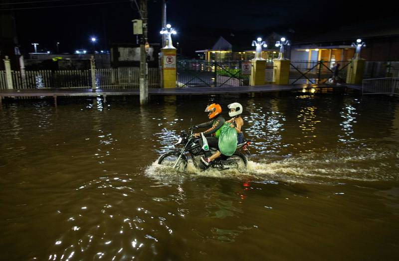 TOPSHOT - People ride on a motorbike along a flooded street in the city centre of Manaus, capital of the Brazilian Amazonas State, on May 31, 2021. - The water level of the Rio Negro, a tributary of the Amazon river, reached 29,97 metres, the same record level as in the 2012 flood season. Manaus and 35 other cities have decreed a state of emergency due to the overflowing of the river. (Photo by Michael DANTAS / AFP)