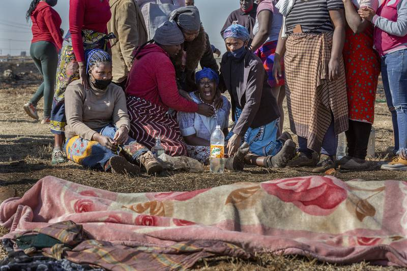 Family members mourn next to the body of a fifteen-year old boy who was allegedly shot dead by taxi association members attempting to disperse looters in Vosloorus, Johannesburg, Wednesday, July 14, 2021. Rioting has continued in parts of South Africa, in unrest sparked by the imprisonment last week of ex-President Jacob Zuma that has spiralled into days of looting in two of the country's nine provinces. (AP Photo/Yeshiel Panchia)