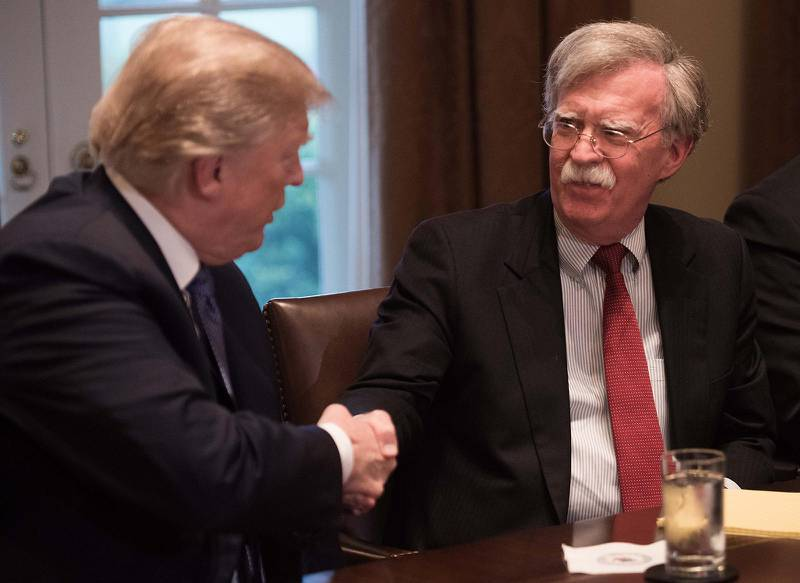 """(FILES) In this file photo taken on April 9, 2018, US President Donald Trump shakes hands with National Security Advisor John Bolto during a meeting with senior military leaders at the White House in Washington, DC. - US President Donald Trump on September 10, 2019, announced he has fired his hawkish national security advisor John Bolton, saying he disagreed """"strongly"""" with his positions. """"I asked John for his resignation, which was given to me this morning,"""" Trump announced on Twitter. """"I informed John Bolton last night that his services are no longer needed at the White House."""" Trump said he would name a replacement next week. (Photo by NICHOLAS KAMM / AFP)"""