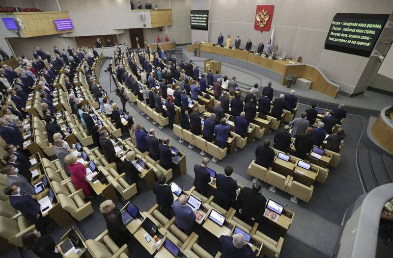 """Deputies, some wearing face masks to protect against the coronavirus disease, listen and sing the national anthem during the first plenary session of the State Duma's autumn session in Moscow on September 15, 2020. (Photo by - / Russia's State Duma PR department / AFP) / RESTRICTED TO EDITORIAL USE - MANDATORY CREDIT """"AFP PHOTO / Russia's State Duma / handout"""" - NO MARKETING - NO ADVERTISING CAMPAIGNS - DISTRIBUTED AS A SERVICE TO CLIENTS"""