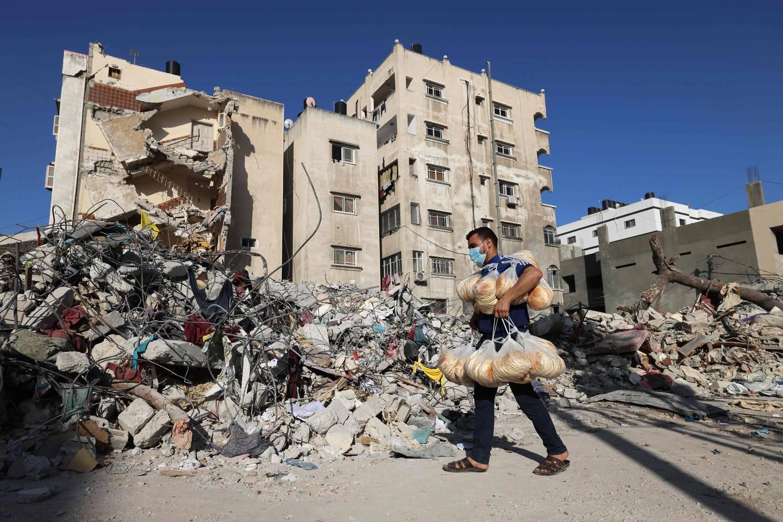 En palestinsk mann går foran ruinene av et ødelagt bygg i Gaza by.