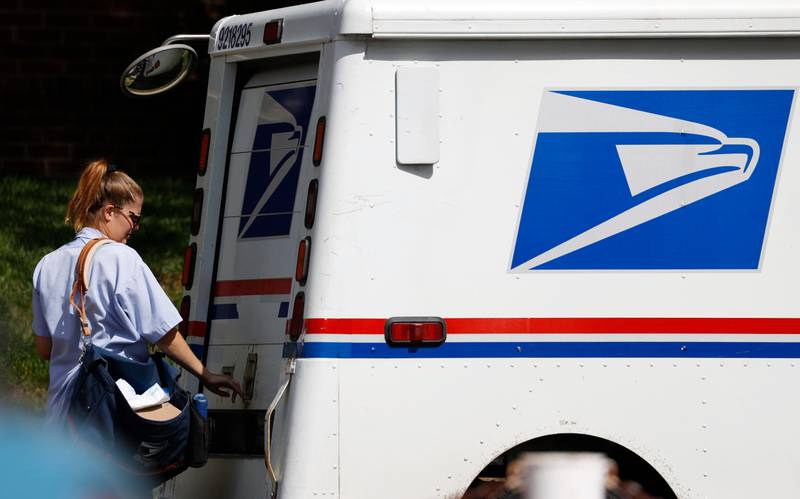 FILE - In this July 22, 2020 file photo a United States Postal Service delivery person closes the back door on her van in Denver. A group of states suing over service cuts at the U.S. Postal Service is asking a federal judge to immediately undo some of them, saying the integrity of the upcoming election is at stake. (AP Photo/David Zalubowski, File)