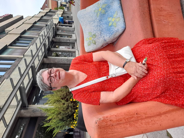 En dame sitter i rød, lang kjole på steinsofaen i gågata, Fredrikstad