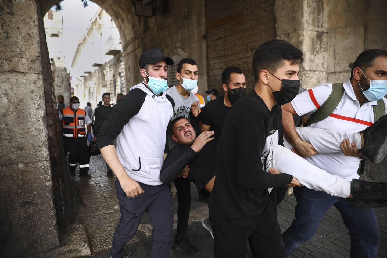 Palestinere bærer vekk en skadd demonstrant gjennom i gamlebyen i Jerusalem. Foto: Oded Balilty / AP / NTB