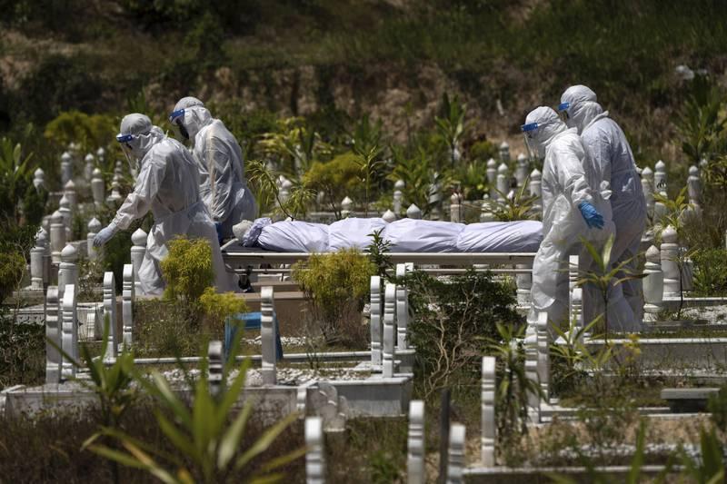 En person som mistet livet med koronaviruset blir båret til sitt siste hvilested på gravplassen Gombak utenfor Kuala Lumpur i Malaysia. Landet står nå midt i en ny smittebølge. Foto: Vincent Thian / AP / NTB