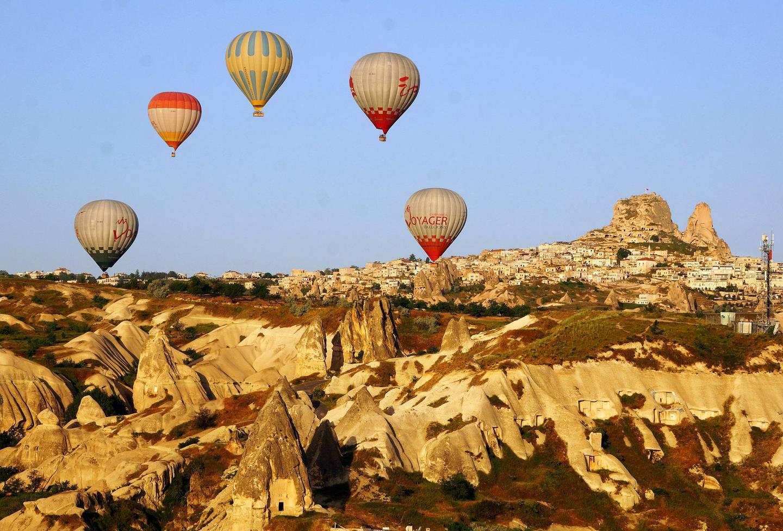 Fly i en luftballong over de snåle fjellene og hulehusene i Kappadokia i Tyrkia.