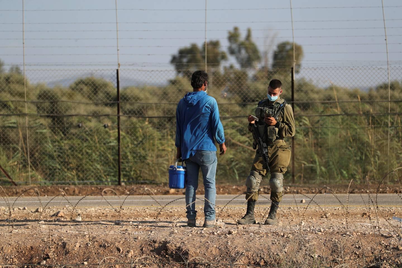 En israelsk soldat sjekker papirene til en palestinsk mann når han krysser grensa tilbake til Vestbredden fra Israel.