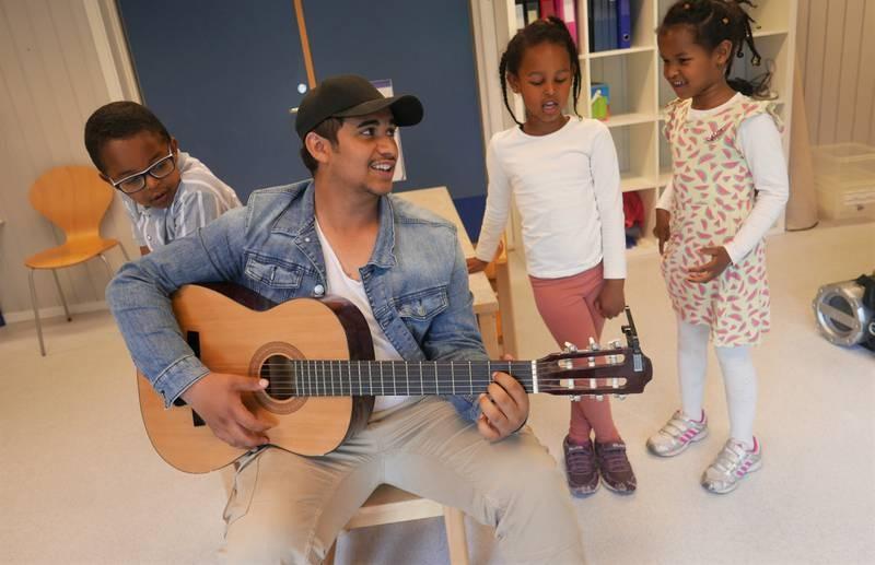 Avdi Tepeku (16) stortrives med sommerjobb i Leie barnehage, hvor musikkglade Sakariye (fra venstre), Sumaya og Sabrin setter pris på at han spiller og synger.