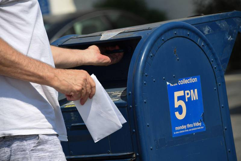 A person mails a letter at a mailbox outside a post office in Los Angeles, California, August 17, 2020. - The United States Postal Service is popularly known for delivering mail despite snow, rain or heat, but it faces a new foe in President Donald Trump. Ahead of the November 3 elections in which millions of voters are expected to cast ballots by mail due to the coronavirus, Trump has leveled an unprecedented attack at the USPS, opposing efforts to give the cash-strapped agency more money as part of a big new virus-related stimulus package, even as changes there have caused delays in mail delivery. (Photo by Robyn Beck / AFP)