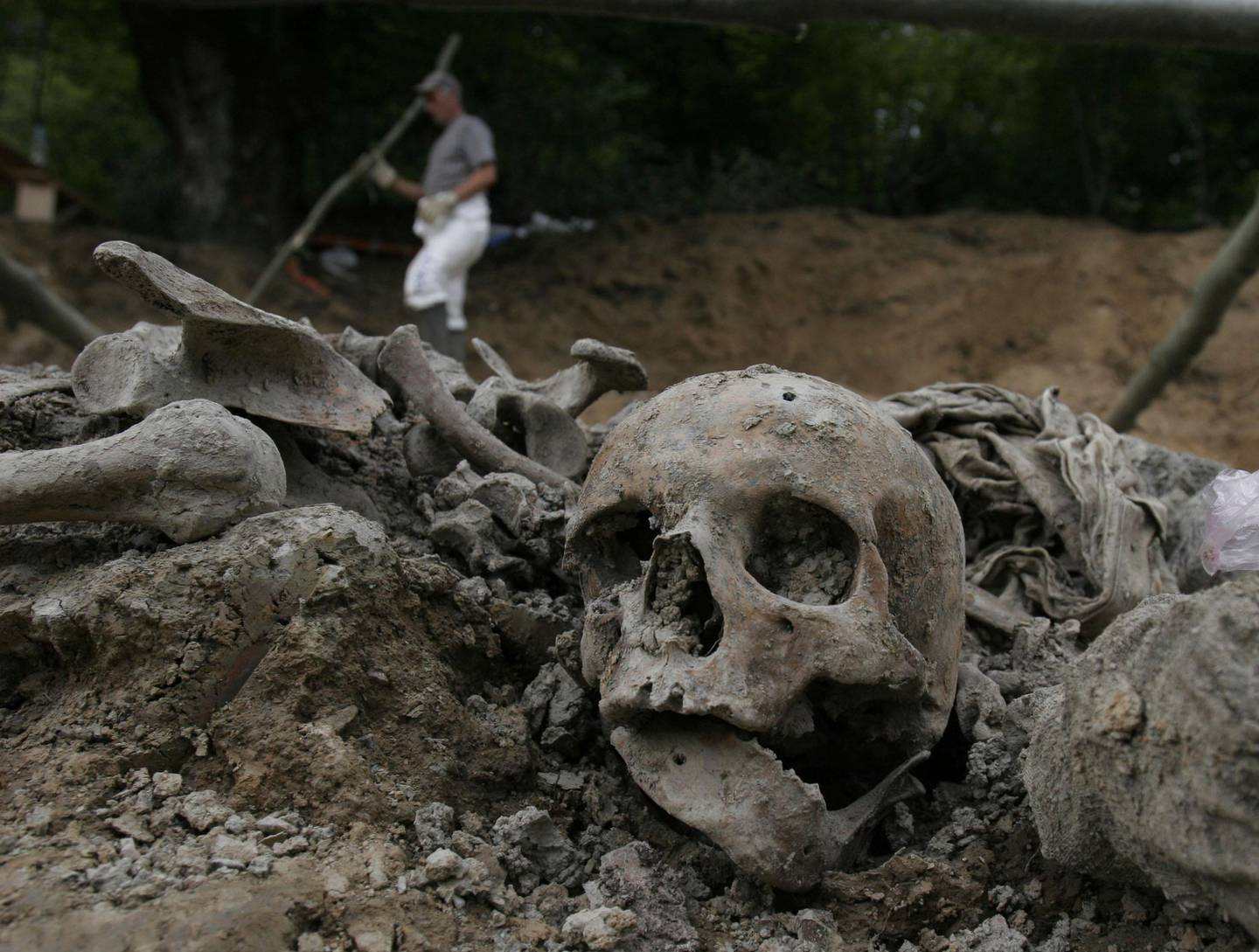 FILE - A July, 10, 2007 file photo shows a Bosnian worker passing by a human skull during exhumation at a mass grave site in a village of Budak, near Srebrenica, Bosnia-Herzegovina. Former Bosnian Serb Army chief Ratko Mladic will learn his fate on Nov. 22, 2017, when U.N. judges deliver verdicts in his genocide and war crimes trial. (AP Photo/Amel Emric, File)