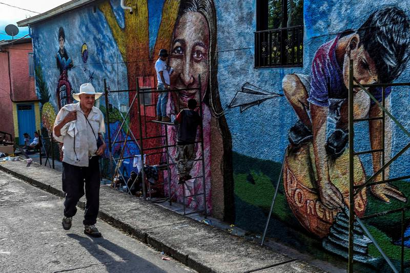 A man walks next to a mural while artists paint during the First International Mural Festival for Peace in San Carlos, Antioquia department, Colombia on November 20, 2018. - San Carlos is located in a strategic geographic region where paramilitary and guerrilla groups fought for territory control. According to the event organizers the Mural Festival is aimed at changing the negative perception of the town, known mostly for its violent past, into a site open to tourism that offers good accommodation facilities, activities such as ecotourism and now adds a circuit of  56 murals to tour. (Photo by JOAQUIN SARMIENTO / AFP)