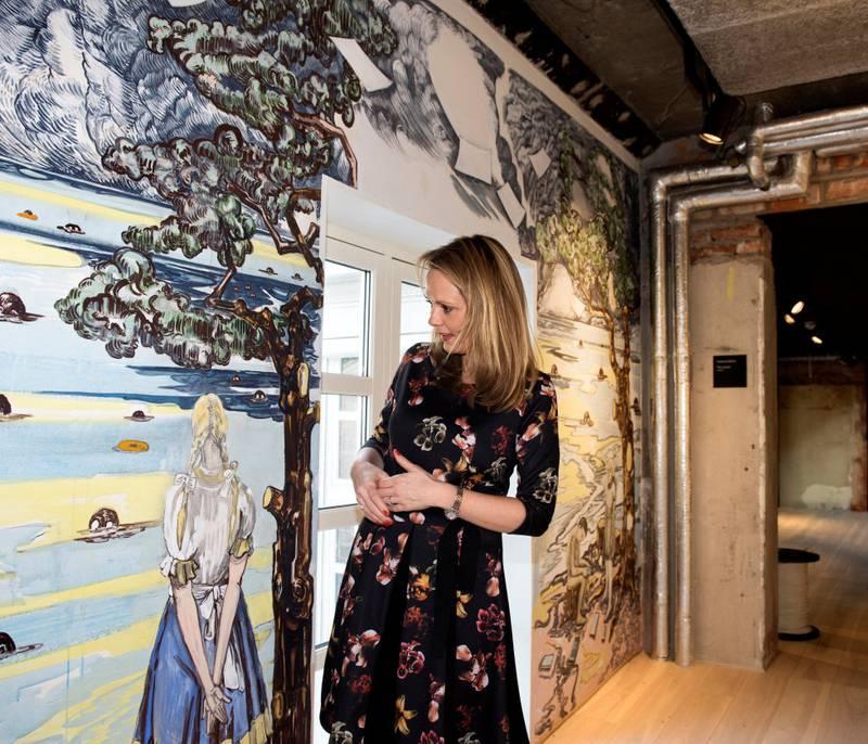 Kulturminister Linda Hofstad Helleland tar Vanessa Bairds veggmaleri på kultur- og innovasjonshuset Sentralen i nærmere øyesyn.