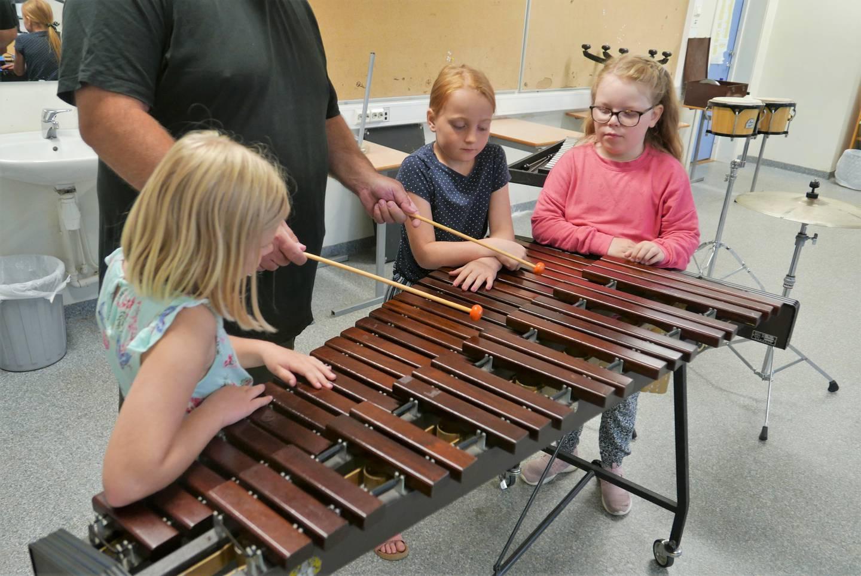 "Knut Lothe viser Sofie (9), Amanda (8) og Lilly (8) hvordan man skal spille ""We will rock you"" på xylofon."
