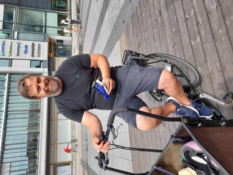 En smilende mann sitter på en sykkel med vogn foran. Han holder en is