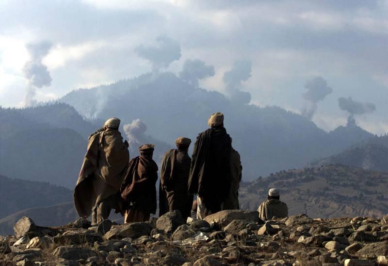 USA slo raskt tilbake mot al-Qaidas tilholdssted Afghanistan etter terrorangrepene 11. september. Afghanere som kjempet mot Taliban ser på eksplosjonene etter amerikanske bombeangrep i Tora Bora-fjellene i desember 2001.