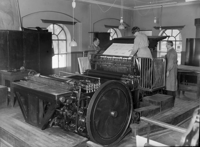 Påleggerske og trykker i Statens Kartverks trykkeri i St. Olavs gate 32 cirka 1923. Hurtigpressa «Johannisberg» fra 1903 var i bruk til trykking av sjøkart i format 85x110 cm fram til 1959.