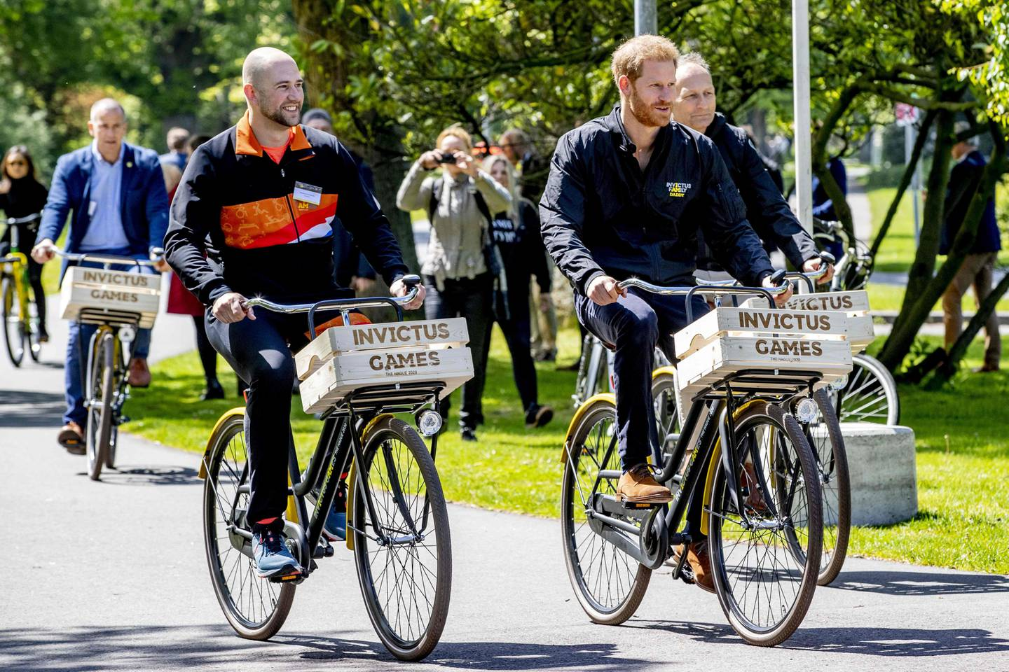 Former Dutch serviceman and athlete Dennis Van Der Stroom (L) and Prince Harry (R) ride a bike during the presentation of the Invictus Games The Hague 2020, in The Hague, Netherlands, on May 9, 2019. - The fifth Invictus Games The Hague 2020, an international sporting event for wounded, injured and sick servicepersonnel, will be held in the Zuiderpark in 2020. (Photo by patrick van katwijk / ANP / AFP) / Netherlands OUT