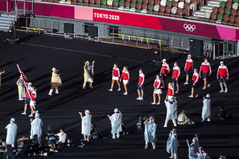 Svømmer Tomoe Zenimoto Hvas og stuper Anne Vilde Tuxen bærer det norske flagget og leder den norske troppen under åpningsseremonien på Olympiastadion i Tokyo. Foto: Heiko Junge / NTB