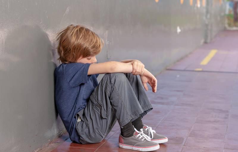 Elementary School. Sad little boy oppressing in the schoolyard. Bullying concept.