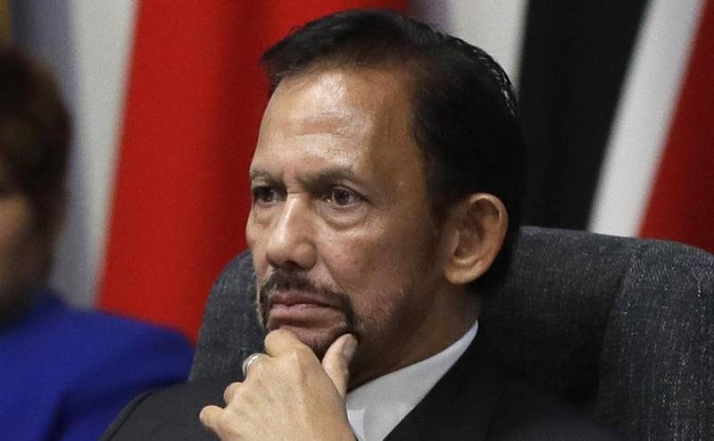 """FILE - In this April 19, 2018, file photo, the Sultan of Brunei Hassanal Bolkiah listens during the first executive session of the CHOGM summit at Lancaster House in London. Brunei's sultan has said a moratorium on capital punishment is in effect for new Shariah criminal laws including stoning people for gay sex and adultery that sparked an international outcry. Sultan Hassanal Bolkiah said Sunday, May 5,  in a speech to mark the start of Ramadan that he was aware of the """"many questions and misperceptions"""" over the penalties provided for under new sections of Brunei's Shariah Penal Code, but stressed that there should be no fear.(AP Photo/Kirsty Wigglesworth, File)"""