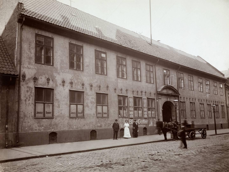 Stiftsgården i Rådhusgata 13 det året den ble revet, i 1913. Her holdt Banan-Matthiessens bananmodneri til. I vinduene reklame for «Jamaica Bananer» og på veggen for Blaa gutter sykkelbud.