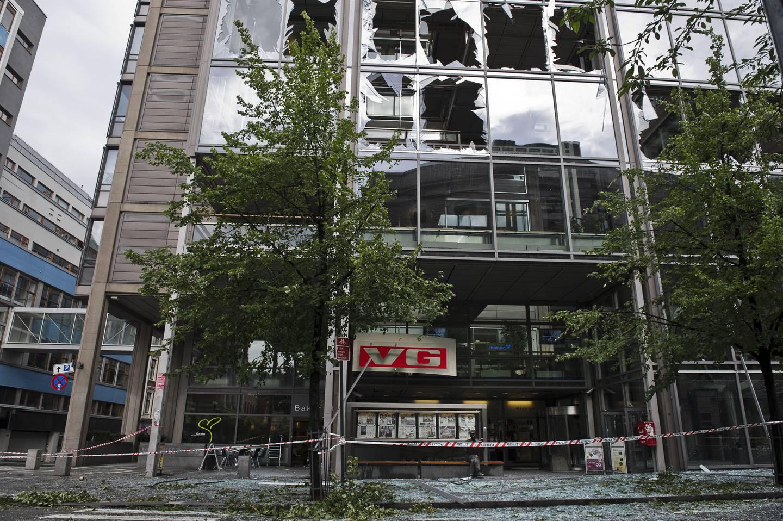 VG-huset med knuste ruter og glass på fortauet foran.
